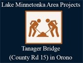 Two construction workers moving dirt with words that say Lake Minnetonka Area Projects for Tanniger Bridge in Orono